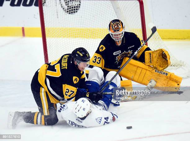 Owen Tippett of the Mississauga Steelheads ''is taken down by Riley McCourt in front of goalie Kaden Fulcher of the Hamilton Bulldogs during game...