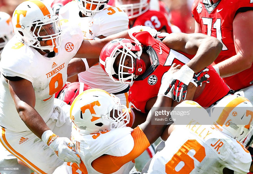 Owen Williams #58 of the Tennessee Volunteers is flagged for a facemask penalty as Williams, Derek Barnett #9 and Todd Kelly Jr. #6 of the Tennessee Volunteers tackle Nick Chubb #27 of the Georgia Bulldogs at Sanford Stadium on September 27, 2014 in Athens, Georgia.