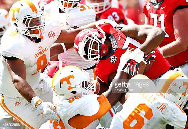 Owen Williams of the Tennessee Volunteers is flagged for a facemask penalty as Williams, Derek Barnett and Todd Kelly Jr. #6 of the Tennessee...