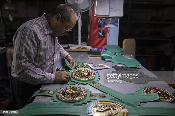 Owner Alberto Reyes examines a newly made World Boxing Council championship belt at the Cleto Reyes manufacturing facility in Ecatepec Mexico on...