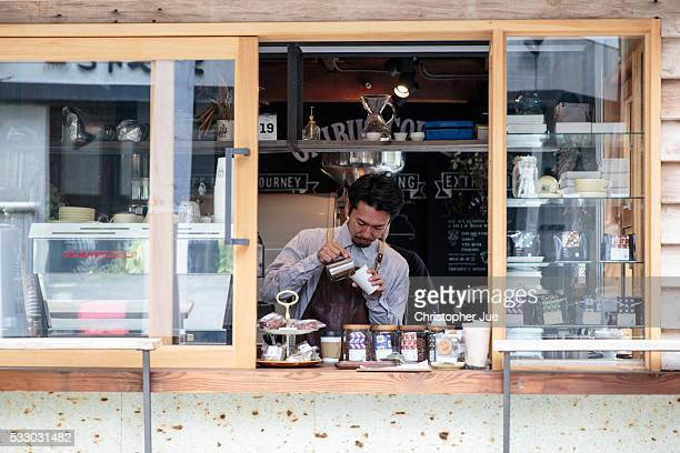 Owner and barista of specialty coffee shop Onibus Coffee Atsushi Sakao prepares a cafe latte on May 20 2016 in Tokyo Japan With the rise of specialty...