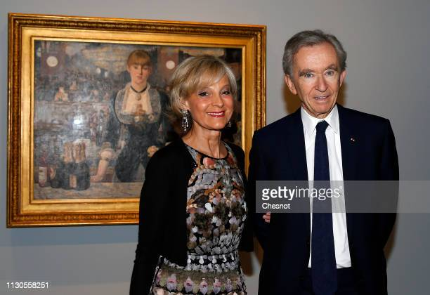 "Owner and CEO of LVMH Luxury Group Bernard Arnault and his wife Helene Arnault pose in front of a painting entitled ""A bar at the Folies-Bergere"" by..."