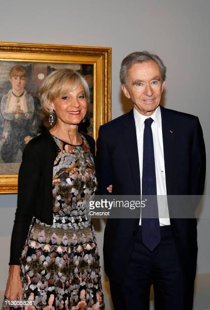 Owner and CEO of LVMH Luxury Group Bernard Arnault and his wife Helene Arnault pose in front of a painting entitled A bar at the FoliesBergere by...