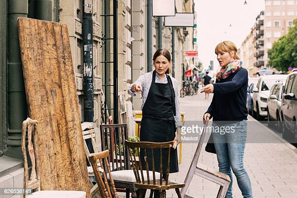 Owner and customer pointing towards chair outside antique shop