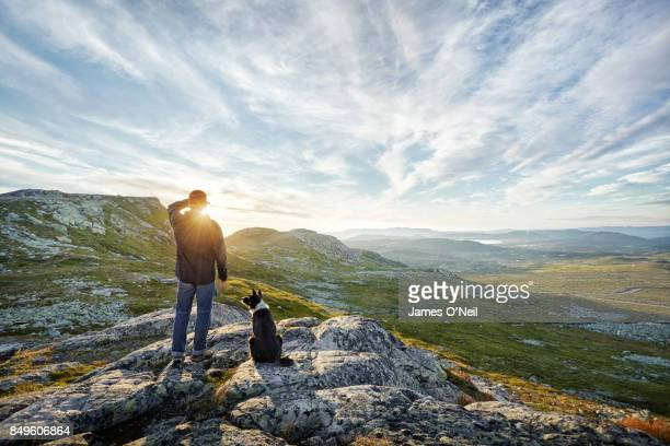 owner and dog watching sunrise in mountainous landscape - nature stock pictures, royalty-free photos & images