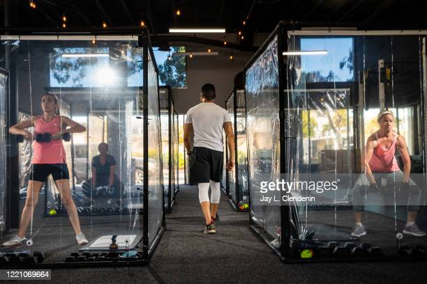 Owner and head coach Peet Sapsin walks between Jennie Reynoso, left and Diane Gloor, right, working out in their Gainz Pods, during his HIIT class,...