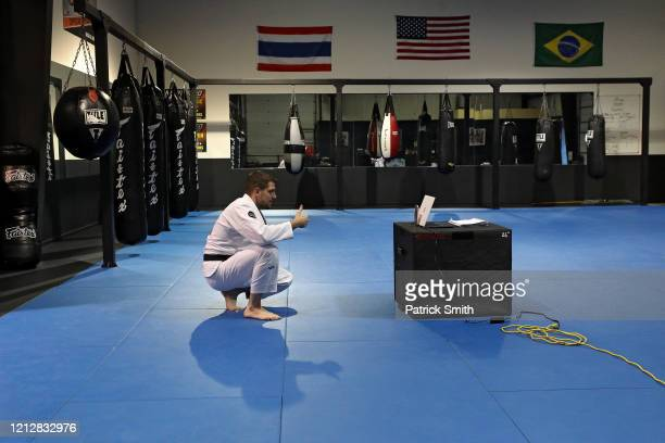 Owner and operator of Method MMA, Eddie Abney interacts with his customers as he broadcasts Facebook live video following Brazilian jiu-jitsu...