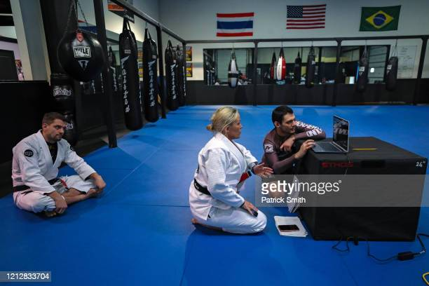 Owner and operator of Method MMA Eddie Abney looks on as his wife Michelle Abney and professional jiujitsu competitor Ellis Karadag troubleshoot to...