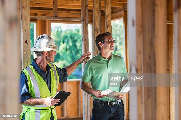 Owner and worker inspecting house under construction