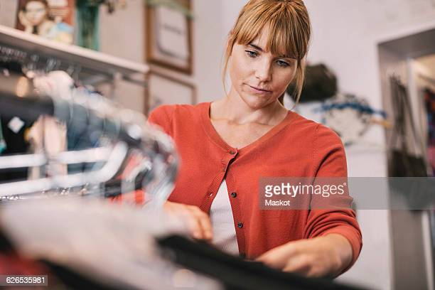 Owner arranging clothes on rack at store
