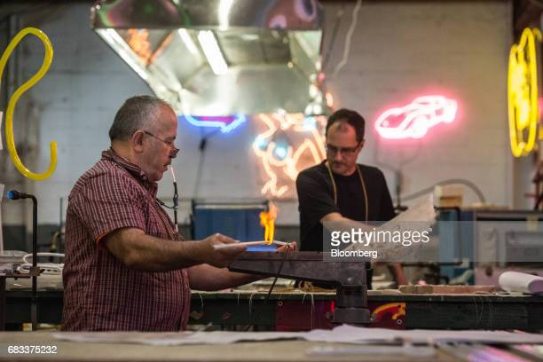 Owner David Ablon right and an employee prepare glass tubing for production at the Precision Neon studio the Brooklyn borough of New York US on...