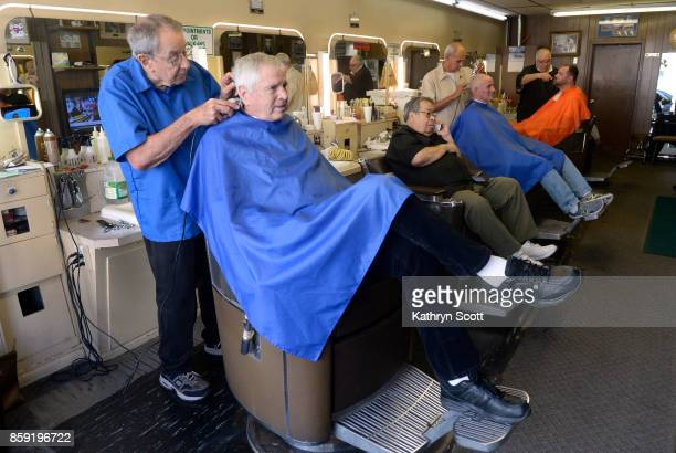 Owner Dick Alderson left and other fellow barbers at O'Briens Barbershop give haircuts to loyal customers on October 3 2017 in Denver Colorado...
