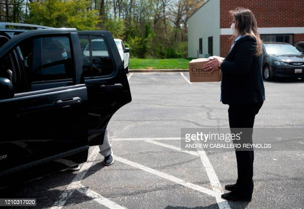 Owner Dorota Marshall stands in the parking lot wearing a mask as she prepares to pass an urn of ashes to a family member picking them up outside...