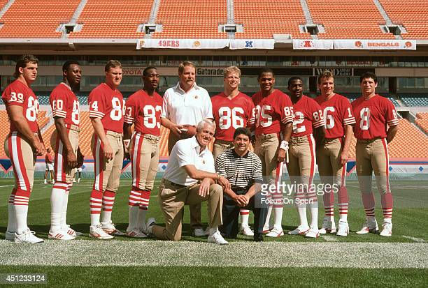 Owner Eddie DeBartolo Jr on a knee and head coach Bill Walsh of the San Francisco 49ers poses together with offensive coordinator Mike Holmgren and...
