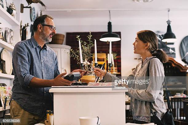 Owner giving credit card to female customer while standing at shop counter