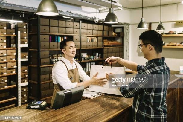 owner giving shopping bag to customer at checkout - customer focused stock pictures, royalty-free photos & images