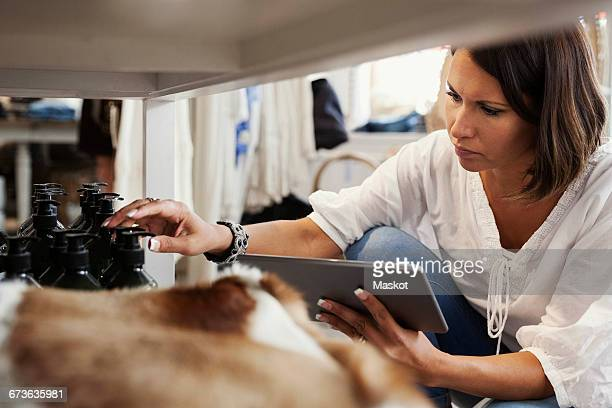 Owner holding digital tablet and checking bottles while crouching at store