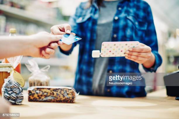 owner holding smart phone while receiving credit card from customer - convenience store counter stock photos and pictures