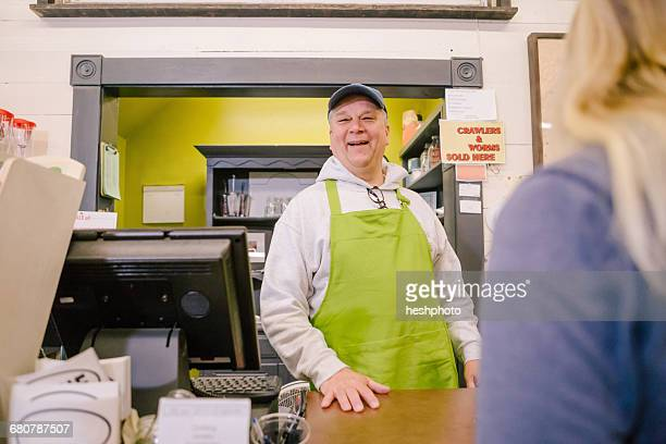owner in general store serving customer at counter - heshphoto stock pictures, royalty-free photos & images