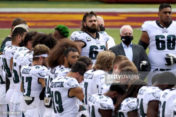 Owner Jeffrey Lurie of the Philadelphia Eagles stands with members of the Eagles and the Washington Football Team during a pregame ceremony at...