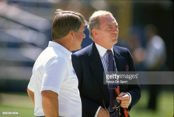 Owner Jerry Jones of the Dallas Cowboys talks with his head coach Jimmy Johnson while on the field prior to the start of an NFL football game circa...