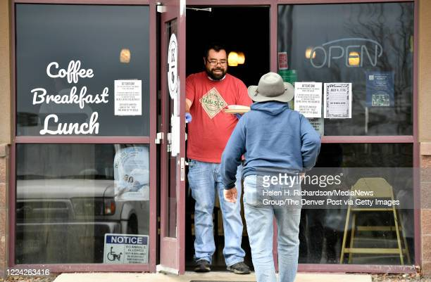 Owner Jesse Arellano hands an order of food to customer Robert Taylor at CC Coffee Kitchen on May 11 2020 in Castle Rock Colorado The cafe decided to...
