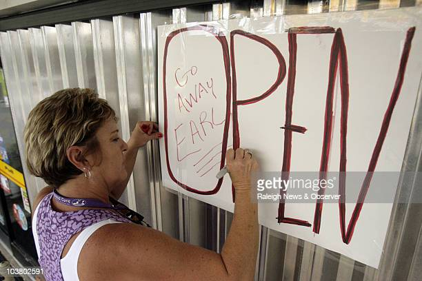 Owner Kim Hall puts a note for Earl to Go away as she puts an Open sign over the metal shutters at the Island Cove store as Hurricane Earl approaches...