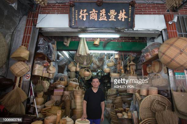 Owner Lin Ding Yuan poses outside the Lin Feng Yi Store in Dadaocheng, Taipei on July 28, 2018. - The store was founded in 1916. The historic area of...