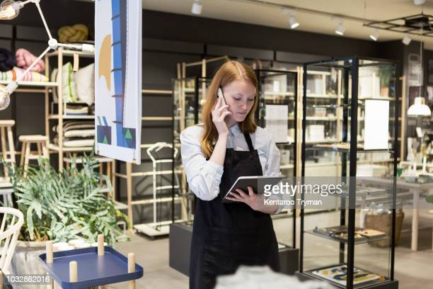 owner looking at digital tablet while talking on smart phone in store - boutique photos et images de collection