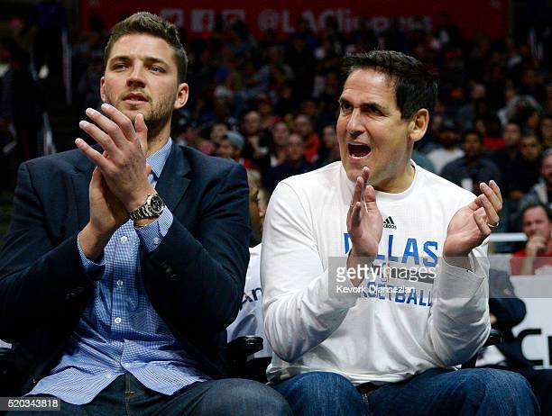 Owner Mark Cuban of the Dallas Mavericks cheers for his team seated next to injured player Chandler Parsons of the Dallas Mavericks during the first...