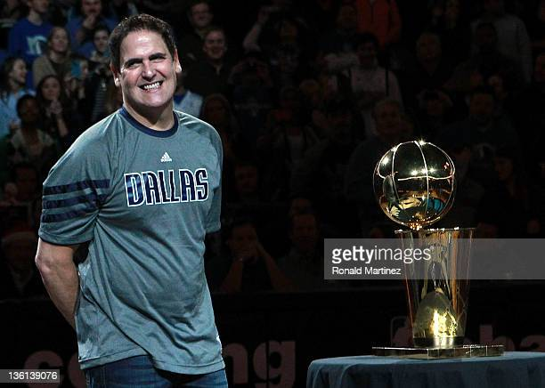 Owner Mark Cuban of the Dallas Mavericks stands with the NBA trophy before a game against the Miami Heat on opening day of the NBA season at American...