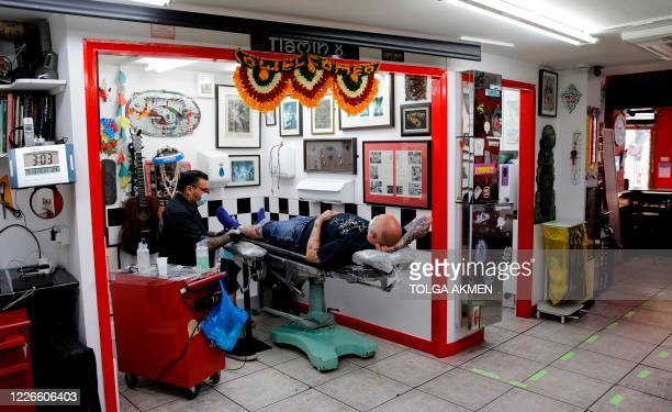 Owner Naresh Bhana wearing a protective face mask works on a design to a customer's leg at the Flamin' Eight tattoo and piercing shop in north London...