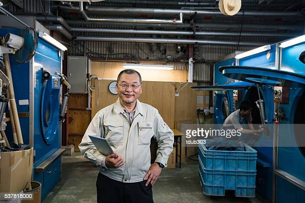 Owner of a large textile factory with digital tablet