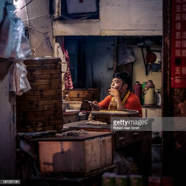 CONTENT] owner of a small steamed dumpling shop sits waiting for customers with a TV remote in hand taken down one of the small lanes of Shanghai