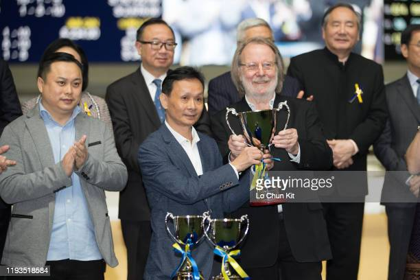 Owner of After Me receives the trophy from Benny Andersson after winning the Race 5 The Swedish Cup at Happy Valley Racecourse on December 11 2019 in...