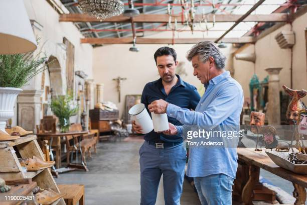 owner of antique shop talking with customer in his store - disruptagingcollection fotografías e imágenes de stock