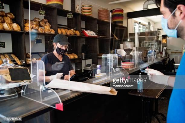 """propietario de una panadería con máscara sirviendo a un cliente. - """"martine doucet"""" or martinedoucet fotografías e imágenes de stock"""