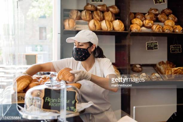 """owner of bakery working with protective gloves and mask. - """"martine doucet"""" or martinedoucet stock pictures, royalty-free photos & images"""