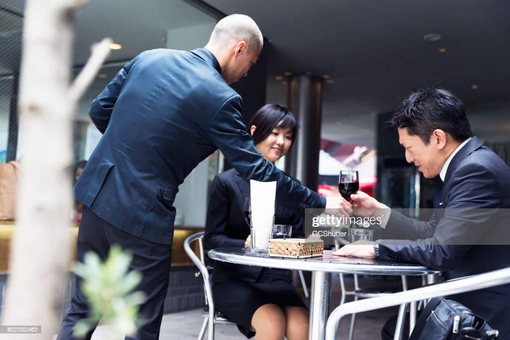 Owner of cafe personally serving his best customers wine : Stock Photo