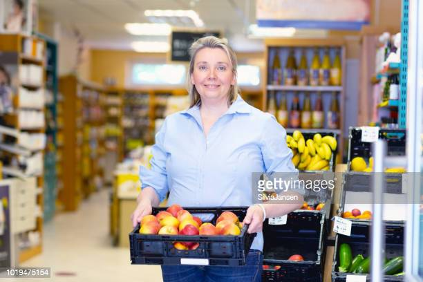 owner of health food store holding box with apples - health food shop stock pictures, royalty-free photos & images