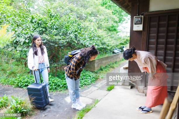 owner of japanese inn greeting female tourists from oversees - south east asian ethnicity stock pictures, royalty-free photos & images
