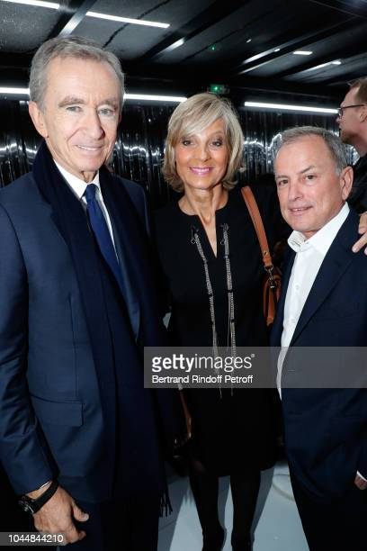 Owner of LVMH Luxury Group Bernard Arnault his wife Helene Arnault and CEO of Louis Vuitton Michael Burke attend the Louis Vuitton show as part of...