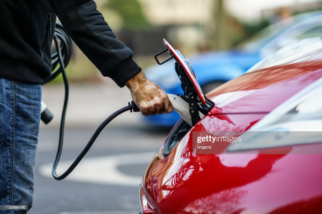 Owner of Nissan Leaf electric car plugged the charger of the car in City Centre of Coventry : Stock Photo