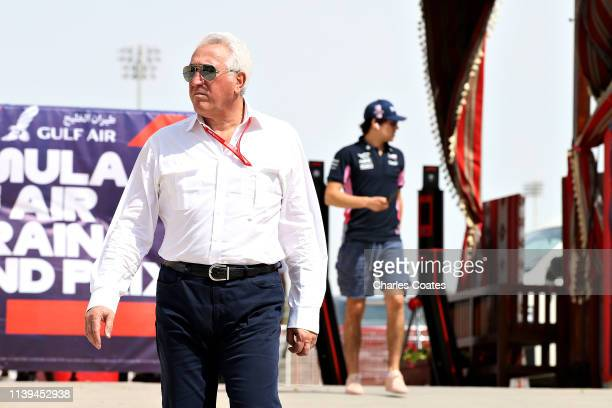 Owner of Racing Point Lawrence Stroll walks in the Paddock followed by son Lance Stroll of Canada and Racing Point before the F1 Grand Prix of...