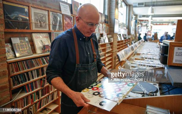 Owner of the Dusty Groove music store Rick Wojcik gets ready to play a special edition vinyl record for his customers during the Record Store Day in...