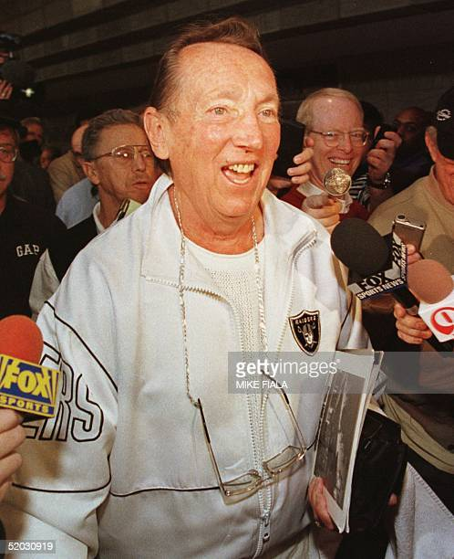 Owner of the Oakland Raiders Al Davis makes his way through a crowd of reporters during the 1999 NFL Annual Meeting 15 March 1999 at the Biltmore...