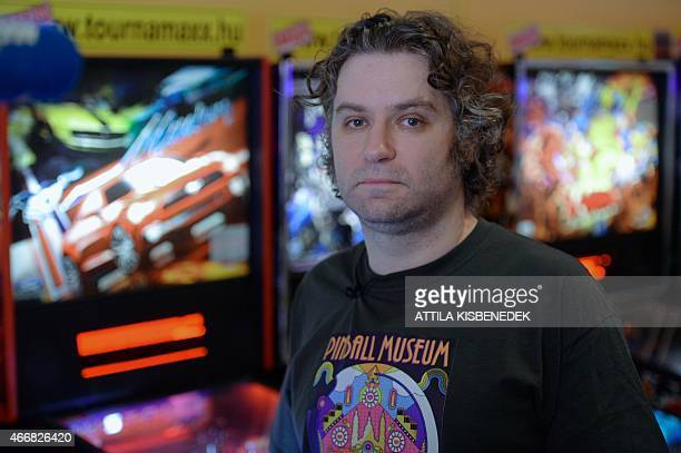 Owner of the 'Pinball Museum' collector Balazs Palfi poses for a photo in a local pub of Budapest in front of some pinball machines on March 14 2015...