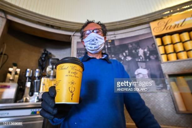 Owner of the Sant'Eustachio cafe Raimondo Ricci poses with a takeaway coffee cup in his establishment on April 30 2020 in Rome during the country's...