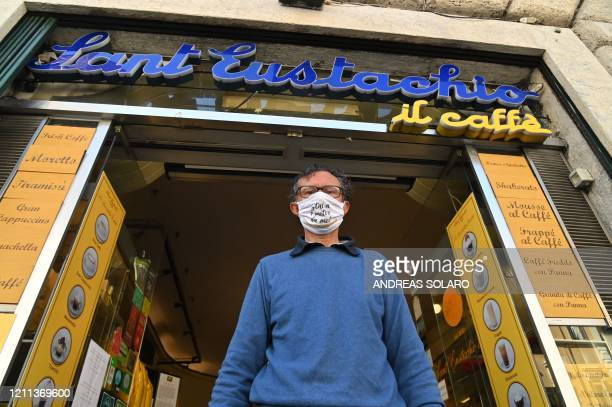 Owner of the Sant'Eustachio cafe Raimondo Ricci wearing a face mask reading Stay one meter away from me poses outside his establishment on April 30...