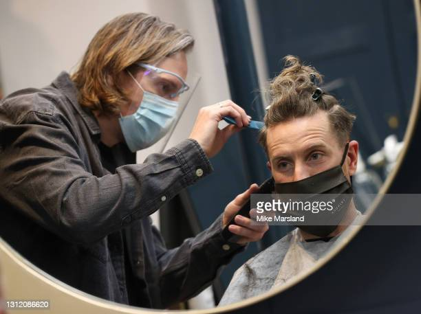 Owner of Trinder Hair Studios, Marc Trinder cuts the hair of his first customer Simon Amphlett after the easing of lockdown restrictions on April 12,...